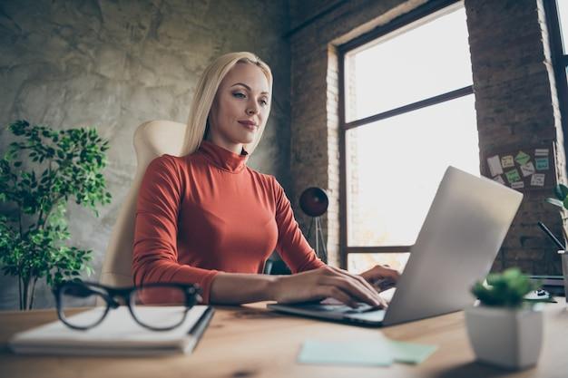 Низко под углом фото квалифицированной бизнес-леди, работающей над своим проектом с ноутбуком, сидя за рабочим столом