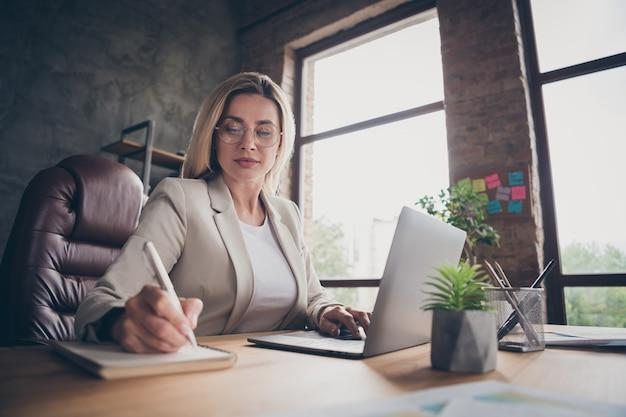 Низко под углом зрения серьезная сконцентрированная женщина замечает, сравнивая данные на ноутбуке с данными в ноутбуке