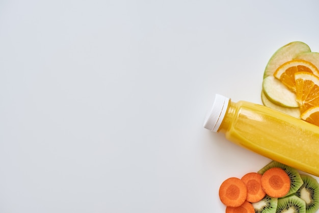 低カロリー食品。白い背景で隔離の果物と新鮮なオレンジ色のスムージー。オレンジ、りんご、にんじん、キウイ