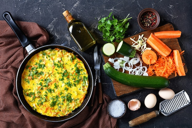 Low-carb zucchini and carrot frittata served on a frying pan on a dark concrete table with a bottle of olive oil, parsley, cutlery, peppercorns, and fresh vegetables, top view, flat lay, close-up