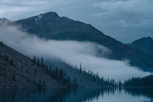 고원 호수 위의 낮은 구름. 짙은 안개에 산 호수를 따라 언덕에 나무의 실루엣. 잔잔한 물에 소나무 반사. 이른 아침에 고산 고요한 풍경입니다. 유령 분위기있는 풍경