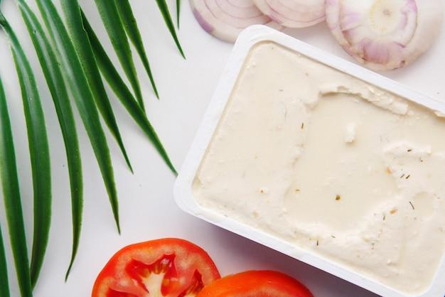 テーブルの上の容器に入った低事実チーズクリーム