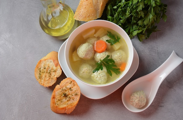 Low fat vegetable soup with chicken meatballs potato and carrot and fresh herbs in bowl