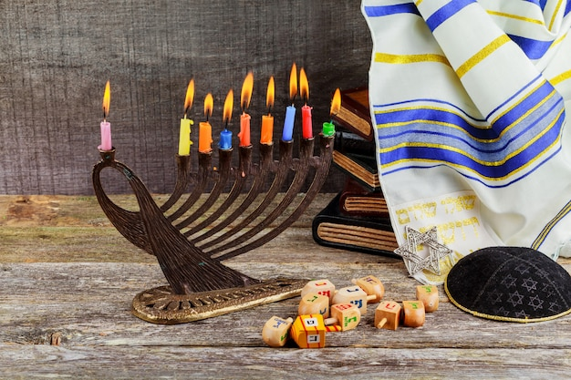 Low key image of jewish holiday hanukkah background with menorah traditional candelabra and burning candles