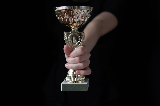 黒にトロフィーカップを保持している女性の低キー画像