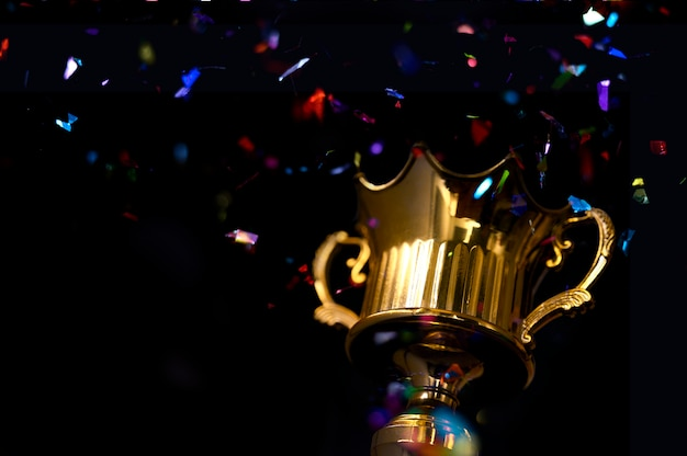 Low key image of trophy  dark background, with abstract glitter lights