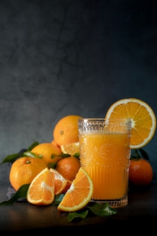 Low key light image of a glass of fresh orange juice next to a set of oranges ready to squeeze