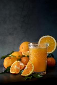 Изображение стакана свежего апельсинового сока рядом с набором апельсинов, готовых к отжиму, при слабом освещении