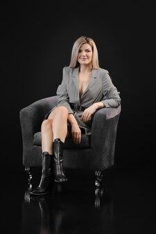 Сдержанный портрет блондинки в сером пиджаке, черном топе и кожаной юбке