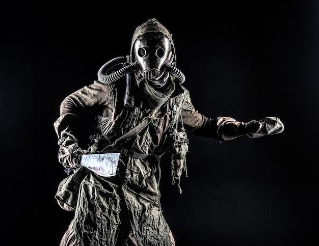 Сдержанный портрет постапокалиптического существа, живущего в мутанте в катакомбах, выжившего в ядерной катастрофе. человек в рваной ткани и противогазе, вооруженный холодным оружием ручной работы, изолированный на черном фоне.