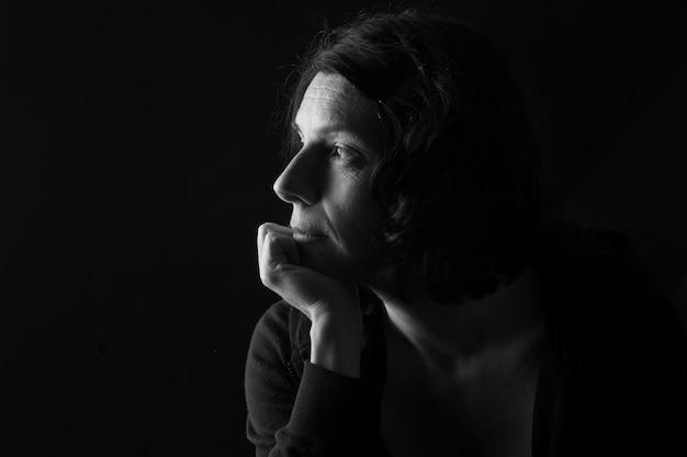 あごに手と黒い部屋で考えている深刻な女性の控えめな肖像画