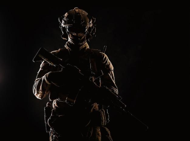 마스크와 안경 얼굴, 전투 헬멧, 전술 무선 헤드셋 뒤에 숨겨진 육군 특수 부대 엘리트 군인의 낮은 키 스튜디오 초상화, 어둠 속에서 돌격 소총 장착 소음기와 서