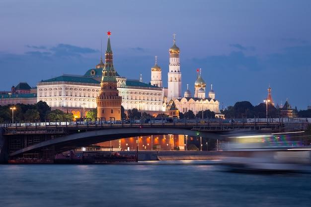 Низкоуровневый вид на кремль в синий час, мост перед ним и размытая лодка на реке