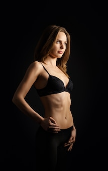 Low ley portrait of pretty girl in black brassiere and dense tights with hand on waist standing in profile