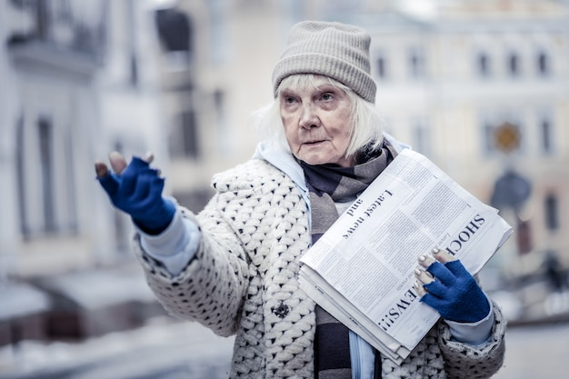 Low paid job. unhappy aged woman earning money while selling newspapers to people
