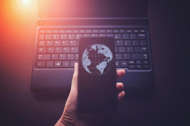 Низкополигональная летающая земля на фоне смартфона. концепция глобального подключения к сети.