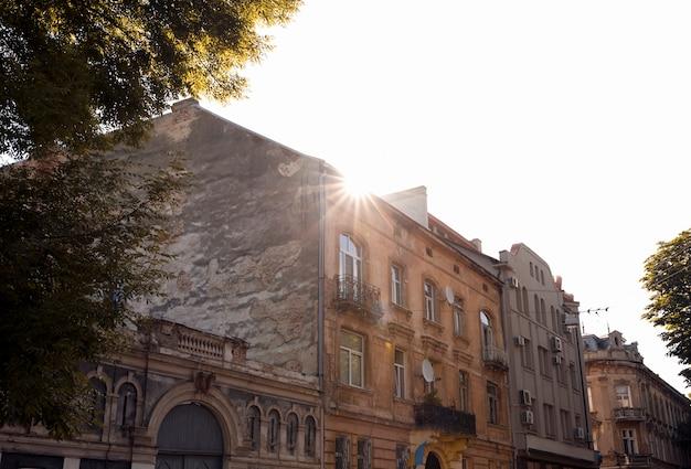 低層のレンガ造りの建物。ウクライナ、リヴィウの太陽フレアのある通り
