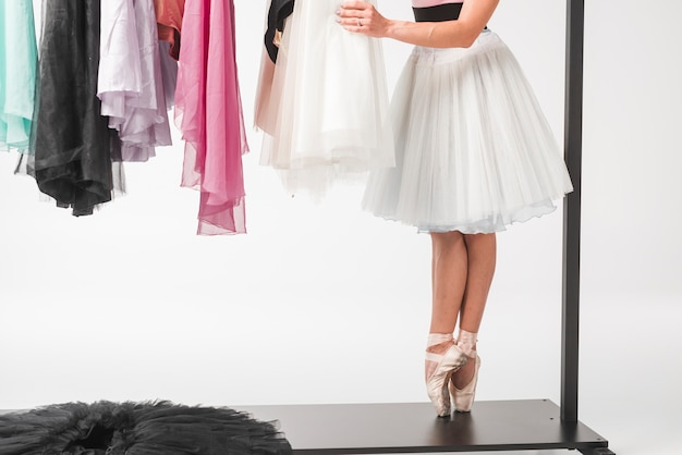 Low section of ballerina standing on mobile clothes rack choosing tutu