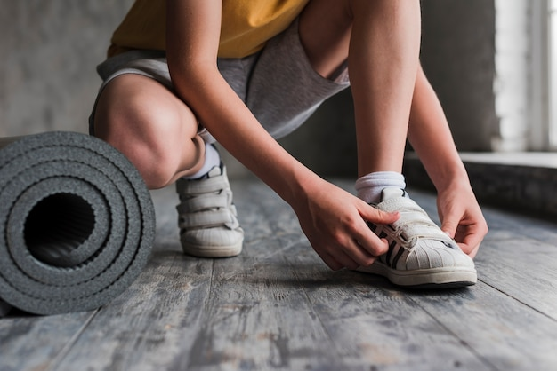 Low section of a boy putting his shoe strap near the rolled up exercise mat