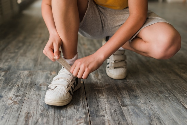 Low section of a boy putting shoe strap on hardwood floor