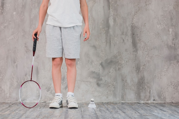 Low section of a boy standing with racket and shuttlecock