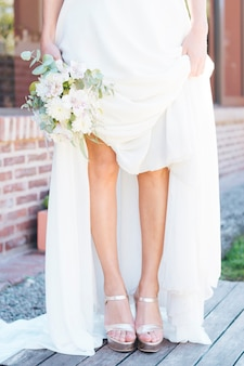 Low section of a bride holding flower bouquet in hand showing her fashionable high heels