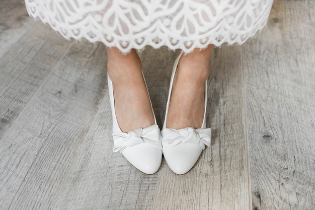 Low section of bride's leg wearing white dress shoes