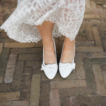 Low section of bride's leg wearing white heels