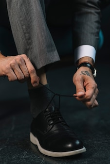 Low section of businessman's hand tying shoelace