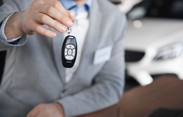 Low section of car salesman with car key