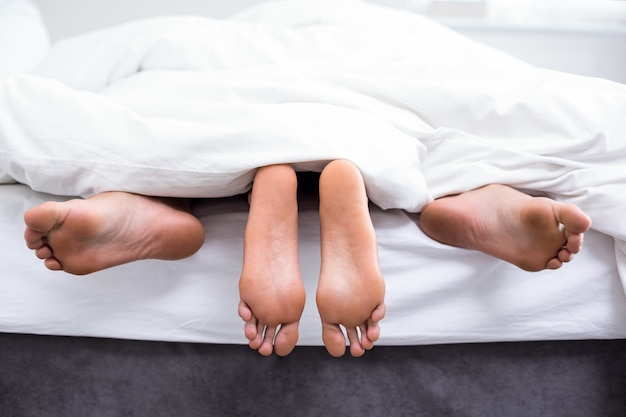 Low section of couple having sex on bed
