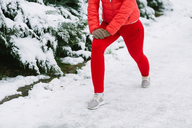 Low section of female athlete exercising on snow