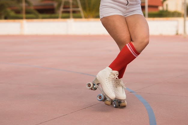 Low section of a female skater balancing with roller skate on court