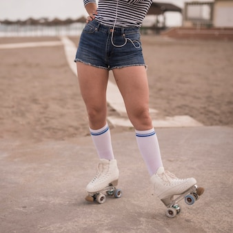 Low section of a female skater standing on the beach