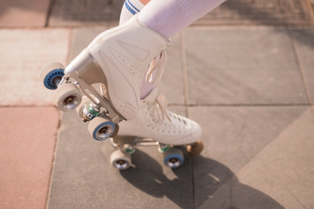 Low section of female skater with white vintage roller skate