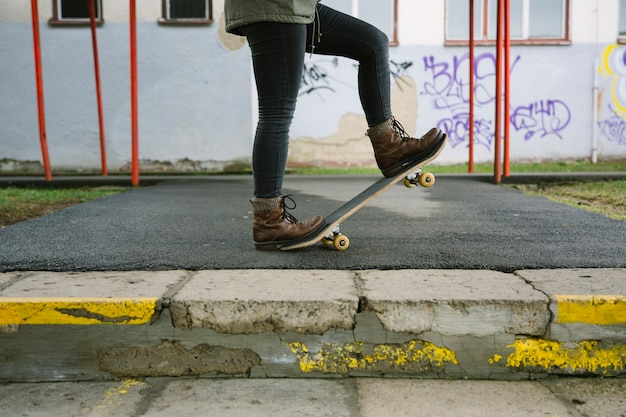 Low section of female standing on skateboard