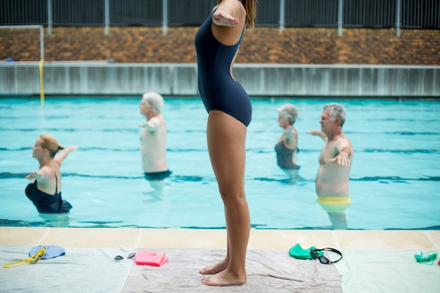 Low section of female trainer preparing senior swimmers