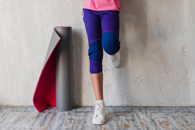 Low section of a girl standing near the rolled up exercise mat