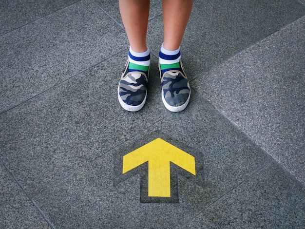 Low section of kid standing in front of yellow directional arrow
