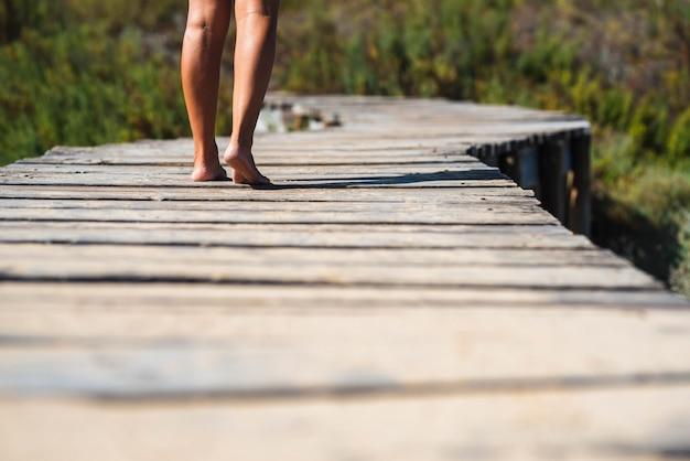 自然林に向かって高架歩道橋を裸足で歩く女性の低いセクションの脚。自然につながる高架橋を前に進む女性の脚の背面図。