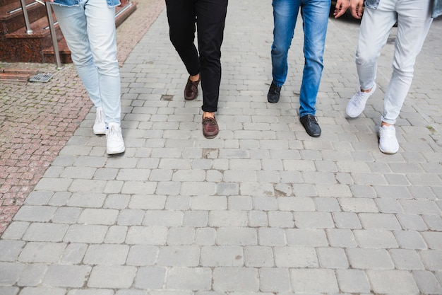 Low section of male friends walking together on pavement