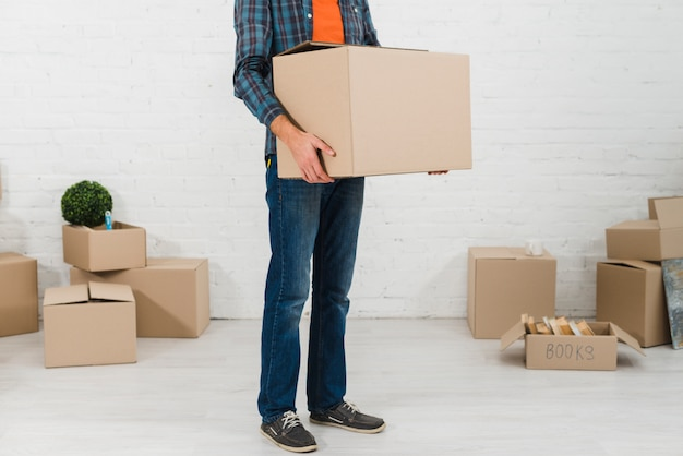 Low section of a man holding cardboard box in his hand