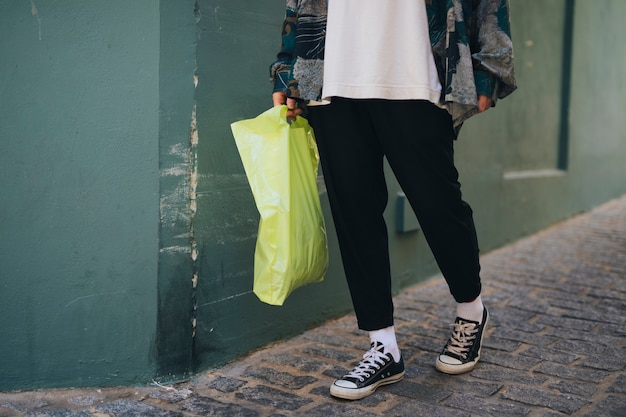 Low section of a man standing near the wall holding green carry bag in hand