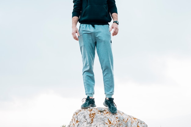 Low section of a man standing on rock against blue sky