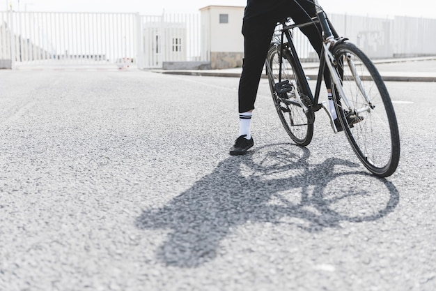 Low section of a man with bicycle standing on road