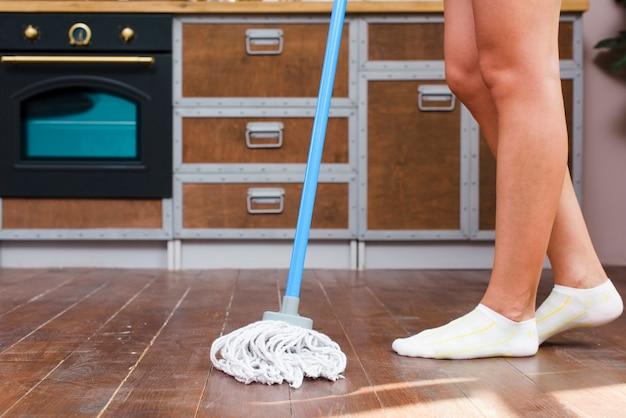 Низкая часть уборщика моет пол на кухне