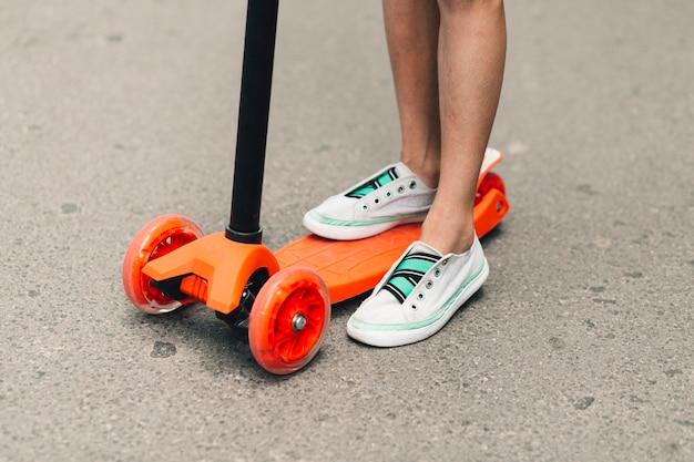 거리에서 오렌지 푸시 스쿠터에 서있는 여자의 낮은 섹션