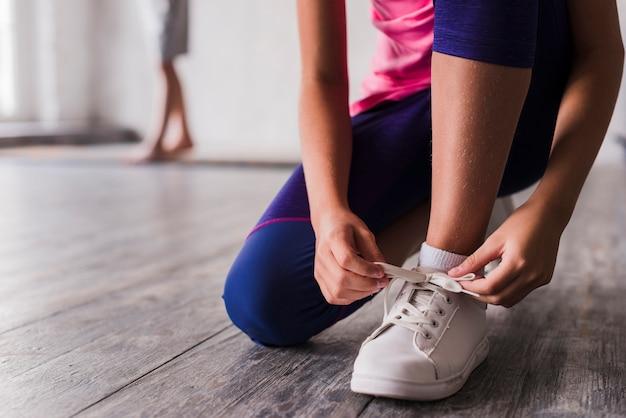 白い靴の靴ひもを結ぶ少女の低いセクション