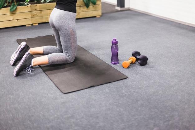 ヨガマットで運動をしている女性の低い部分