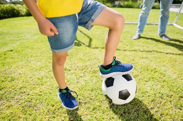 축구에 다리를 가진 소년의 낮은 섹션